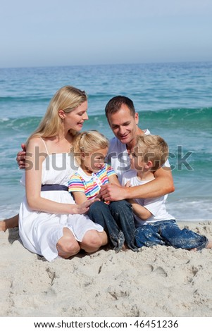 Portrait of an affectionate family sitting on the sand at the beach
