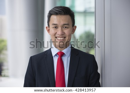 Portrait of an Asian businessman smiling & looking at the camera with blurred office buildings as a background.