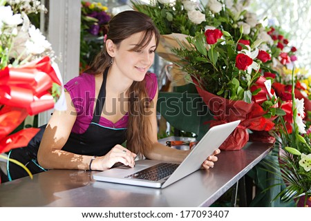 Portrait of an attractive florist business woman owner sitting at a flower shop counter using a laptop computer to place a stock order on line. Small business technology.