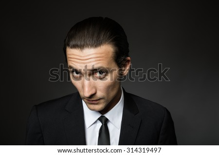 portrait of an attractive mysterious man in black suit and tie on dark background
