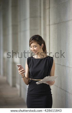 Portrait of an Chinese businesswoman standing outside using her smart phone.