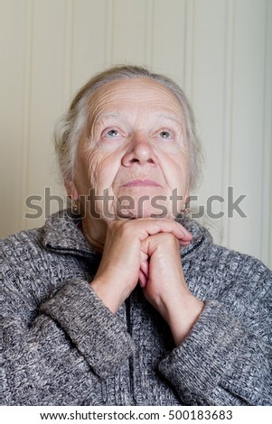 Portrait of an elderly woman with hands near face on a light background.
