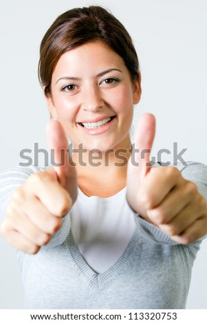 Portrait of an excited young woman gesturing a thumbs up sign