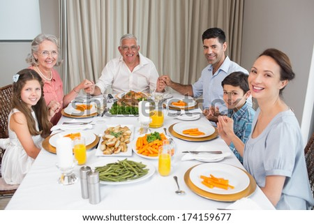 Portrait of an extended family at dining table in the house