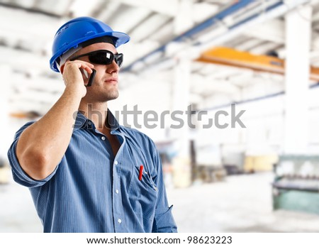 Portrait of an handsome engineer using a mobile phone
