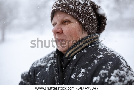 portrait of an old woman in the snow. snowstorm sweeps