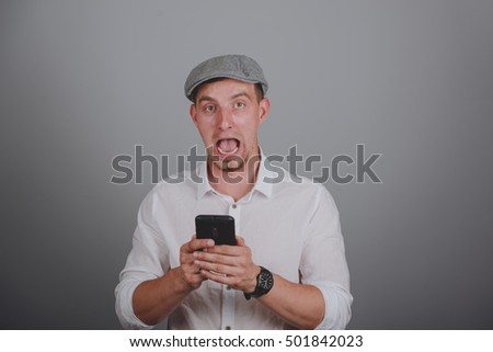 portrait of angry young man shouting using mobile over gray background