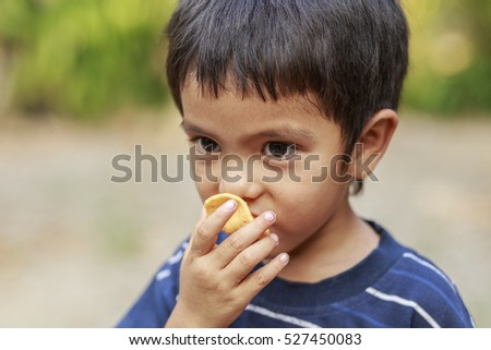 Portrait of Asian little boy eating crisp rice outdoor