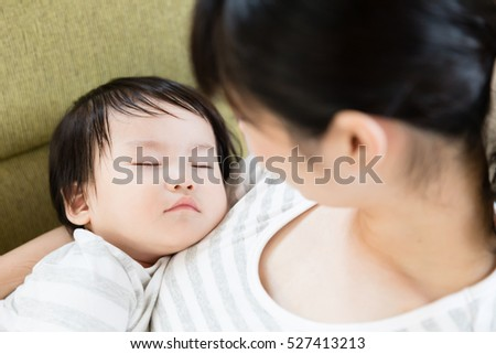 portrait of asian mother and baby relaxing in the living room
