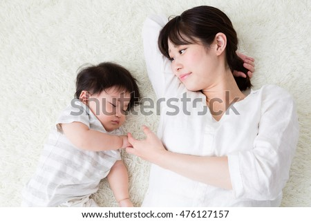 portrait of asian mother and baby sleeping in the room