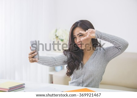 portrait of asian woman take photo of her self using smart phone camera