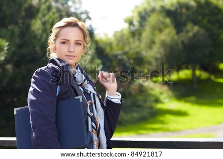 Portrait of attractive businesswoman with park as background, outdoor shoot