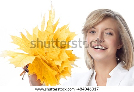 portrait of attractive  caucasian smiling woman isolated on white studio shot looking at camera hand holding yellow marple autumn leaves