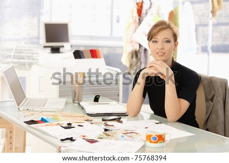 Portrait of attractive female fashion designer sitting at office desk, smiling.