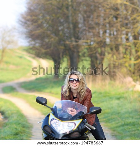 Portrait of attractive girl on sports bike. Biker girl with sunglasses and motorcycle