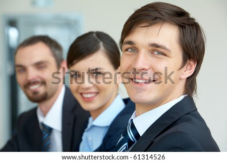 Portrait of attractive male looking at camera with his partners on background