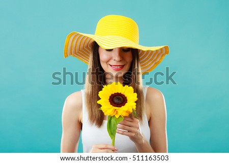 Portrait of attractive summer woman in yellow hat with sunflower in hand on blue background