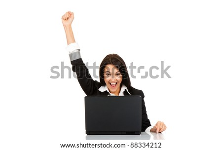 portrait of attractive surprised excited smile business woman sit at desk hold hand up looking at laptop screen, isolated over white background, Winner businesswoman with success