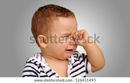 Portrait Of Baby Boy Crying against a grey background
