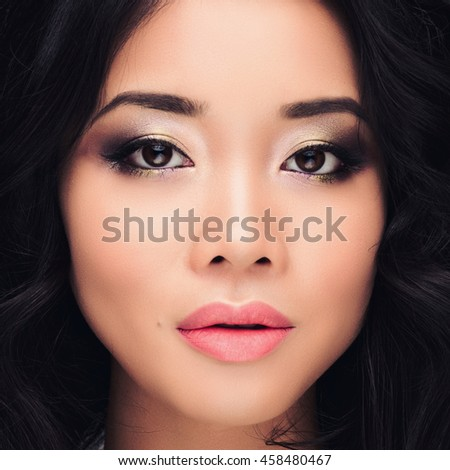 Portrait of beautiful asian brunette girl with a perfectly long curls hair and bright make up, long eyelashes. Beauty studio shooting.