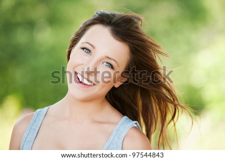 Portrait of beautiful attractive young smiling woman at summer green park