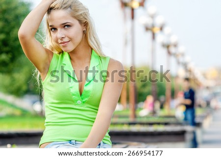 portrait of beautiful blonde girl sitting outdoors. street lamps on background