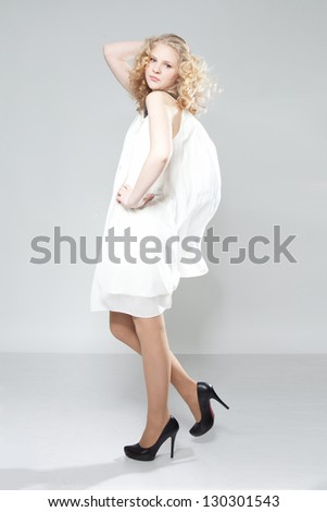 Portrait of beautiful blonde teenage girl in white dress over gray