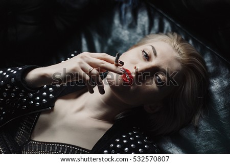Portrait of beautiful blonde woman lying on the sofa and smoking. She has red lips, short hair, white clear skin.