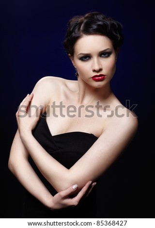 portrait of beautiful brunette girl posing on blue