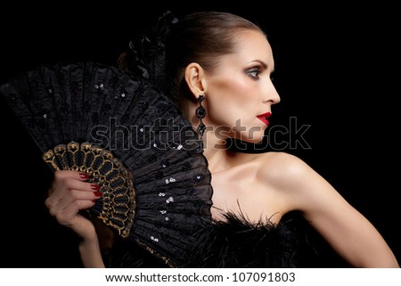 portrait of beautiful brunette woman with black fan in hands