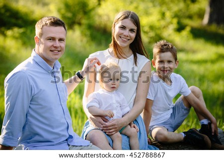 Portrait of beautiful family of four people mother father son daughter sitting on a log picnic in the park near forest