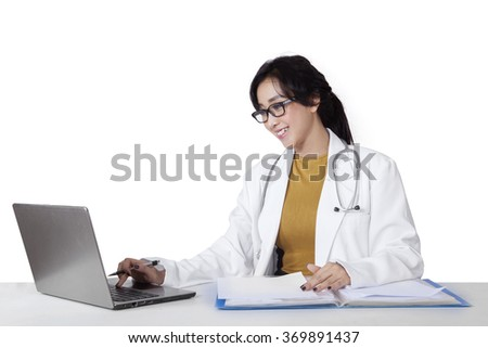 Portrait of beautiful female doctor working on desk with laptop and folder, isolated on white background