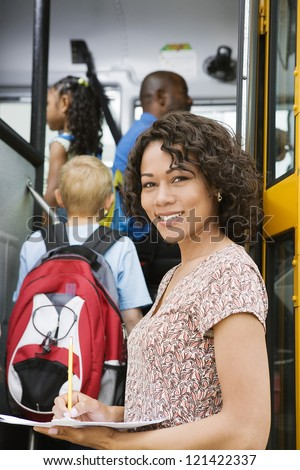 Portrait of beautiful female teacher writing down something on paper while students boarding school bus