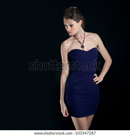 Portrait of beautiful girl with blue dress against black background.