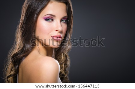 Portrait of beautiful girl with bright pink make-up on grey background. Concept of beauty and fashion