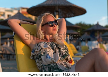 Portrait of Beautiful Happy Smiling Woman Lying on Chair on Beach by Sea