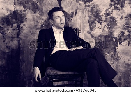 Portrait of beautiful imposing man on vintage wall background. Sits on vintage chair with  cell phone. Blond. Dressed in classic formal suit.  Antique colour graded.