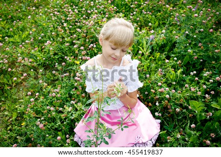 Portrait of beautiful little girl in white dress on the nature