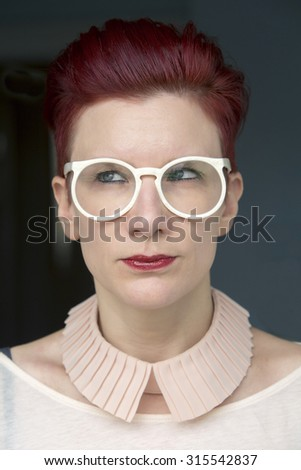 portrait of beautiful red-haired woman wearing white glasses and looking to the side