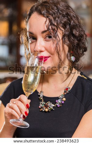 Portrait of beautiful romantic brunette with a champagne glass. Professional make-up on a beautiful woman. A girl sits in a beautiful interior and mysterious looking. Drink, beautiful girl portrait.