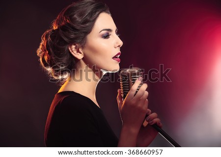 Portrait of beautiful singing woman on red background, close up