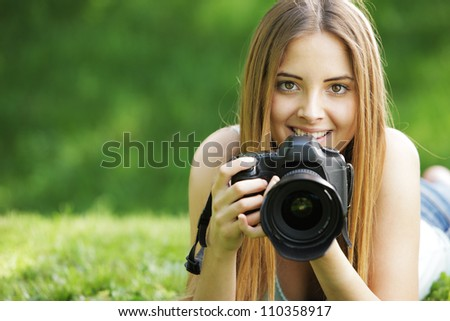 Portrait of beautiful smiling blonde girl , making photos at summer green park.