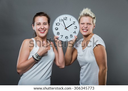 Portrait of beautiful smiling women holding a big clock in her hands.
