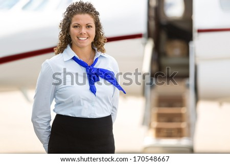 Portrait of beautiful stewardess with private jet in background at terminal