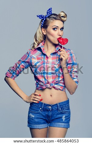 Portrait of beautiful woman eating heart shape lollipop. Caucasian blond model posing in retro fashion and vintage concept studio shoot.
