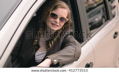 Portrait of beautiful woman in the new car.
