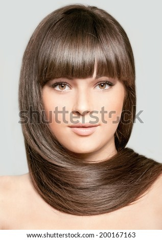 Portrait of beautiful woman with straight long hair on gray background
