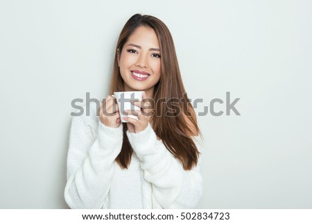 portrait of beautiful young asian in white knitted pullover holding a cup with warm beverage