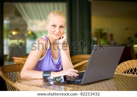 Portrait of Beautiful young blond girl having fun with her laptop at a coffee shop.