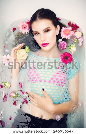 Portrait of beautiful young brunette girl with bright makeup lying in the bath with flowers, the concept of health and beauty
